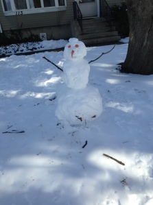 A snowman keeping cool in the shade.
