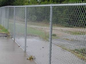 The typical surroundings at most schoolyards and tracks across America are chain link fences.