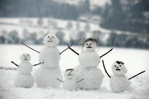 A family of snowman competitors does calisthenics before the start of the race.